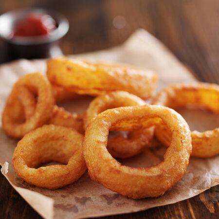 comida rapida: aros de cebolla crujientes con salsa de tomate en el papel de pergamino
