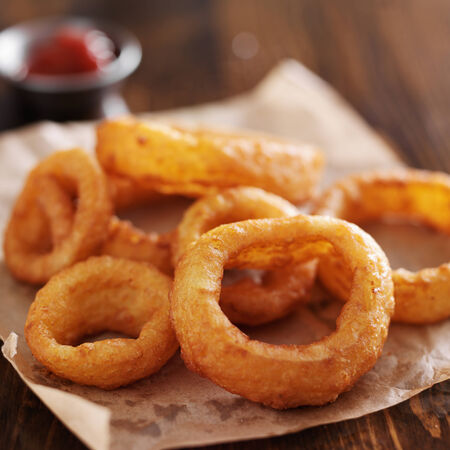 fried food: crispy onion rings with ketchup on parchment paper