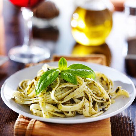 バジル ペストソースをかけて夜に夕食のテーブル上でイタリアのフェットチーネ