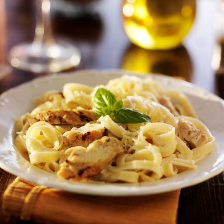 fettuccine alfredo pasta with grilled chicken at night time dinner photo