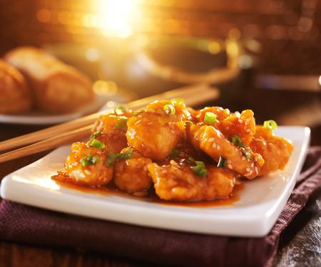 chinese food - sesame chicken with chopsticks Foto de archivo