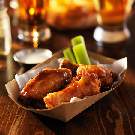 basket of barbecue buffalo chicken wings with celery sticks and ranch sauce photo