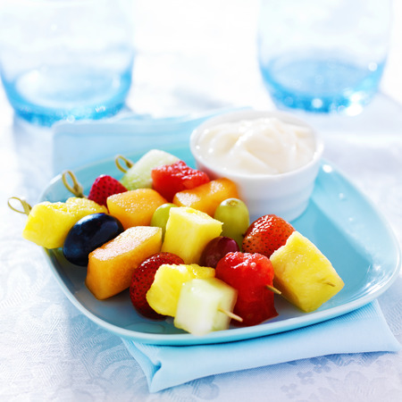 childrens fruit kabob with vanilla yogurt dip on blue plate photo