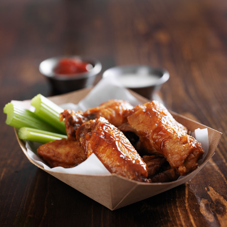 barbecue buffalo chicken wings with celery sticks and ranch sauce Foto de archivo