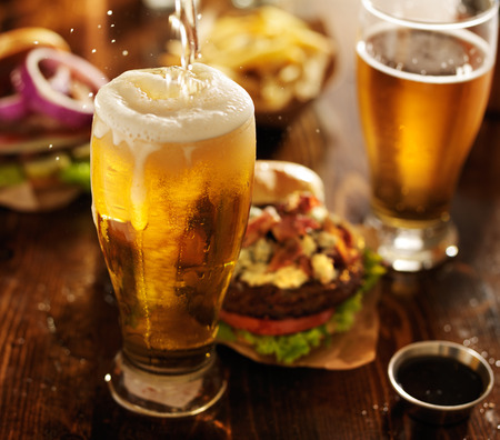 beer drinking: beer being poured into glass with gourmet hamburgers