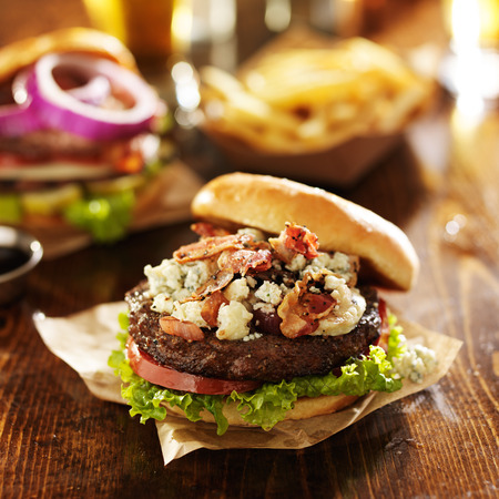 gourmet bacon and bleu cheese burgers with beer Imagens
