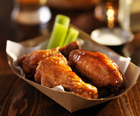 alcohol cardboard: basket of bbq chicken hot wings close up