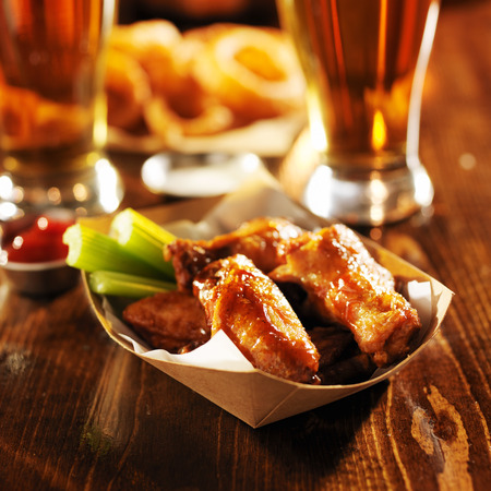 barbecue buffalo chicken wings served with beer, celery, and ranch 스톡 콘텐츠