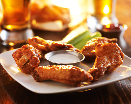 spicy: colorful fried chicken wings in barbecue sauce with ranch and celery