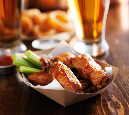 alcohol cardboard: barbecue buffalo chicken wings with celery sticks and ranch sauce Stock Photo