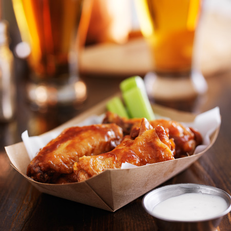 buffalo chicken wings in basket with celery, ranch, and beer Stock Photo