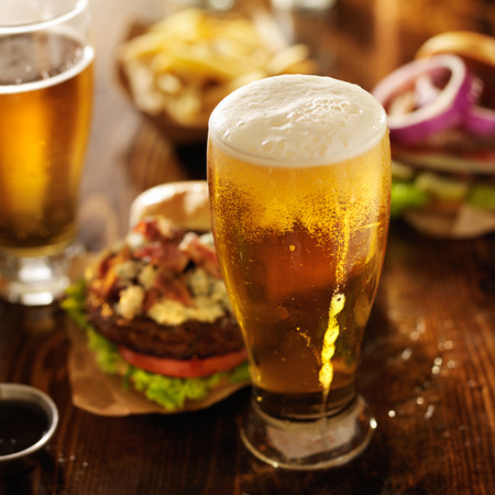 beer in bar: cold beer with foamy head and burgers