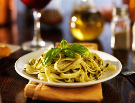 Italiaans fettuccine in basilicum pesto saus op tafel in de nacht