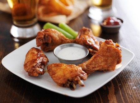 fried food: buffalo barbecue hot chicken wings around ranch sauce with celery Stock Photo