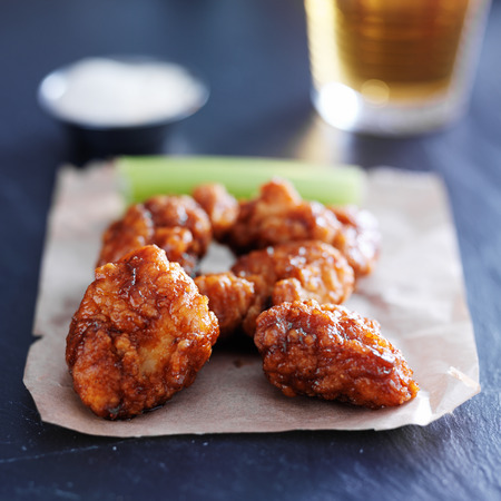 chicken wing: boneless barbecue chicken wings with beer on slate surface