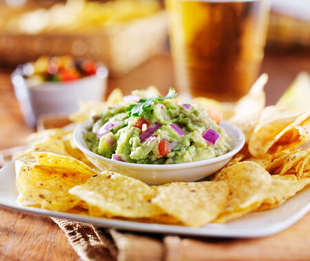 mexican guacamole with tortilla chips and beer