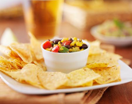 tortilla de maiz: mexicano maíz tostado fuego y salsa de frijol negro con chips de tortilla y cerveza