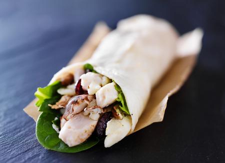 chicken spinach mushroom wrap on slate Standard-Bild