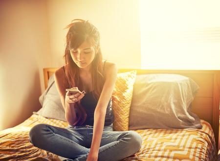 Technophiles asiatique adolescente en utilisant un téléphone intelligent en chambre Banque d'images - 33199523