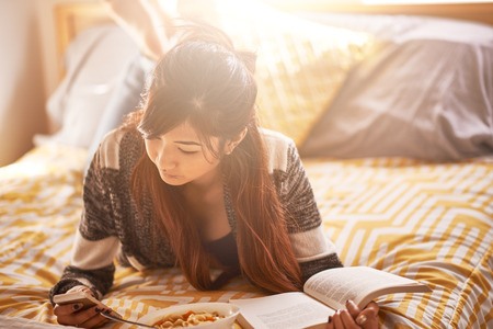asian teen on bed checking smartphone while reading book and eating soup