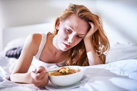 enfermo: comer sopa de fideos de pollo en la cama mientras se está enfermo