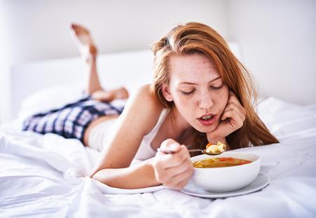sopa de pollo: recuperando la mujer en la cama comiendo sopa de pollo mientras se est� enfermo Foto de archivo