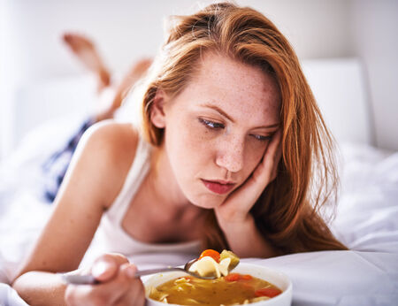 woman with flu in bed with chicken noodle soup photo