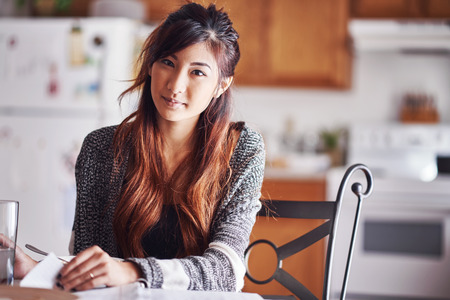 asian teen turning page on document in kitchen