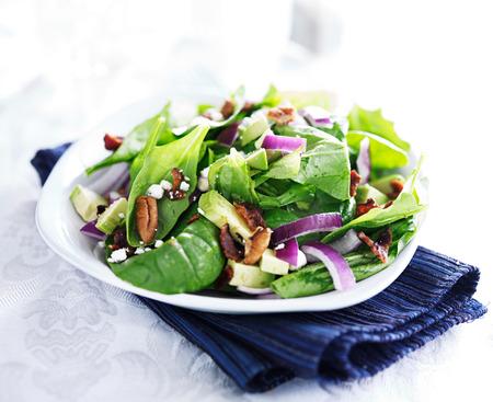 白いプレート上のほうれん草とアボカドのサラダ