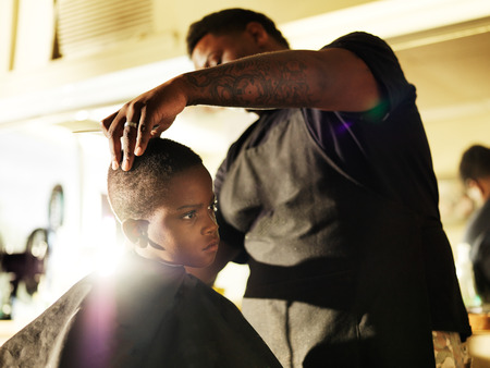 little boy getting his hair cut in barber shop