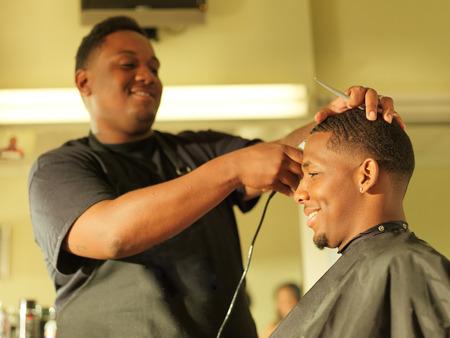 barbero: hombre que consigue un corte de pelo en la barbería Foto de archivo