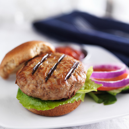 turkey burger on bun with lettuce and fixings photo