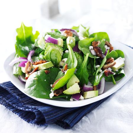 salad plate: espinacas y ensalada de aguacate en la placa blanca