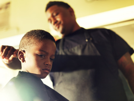 black barber: serious little boy in barber shop Stock Photo