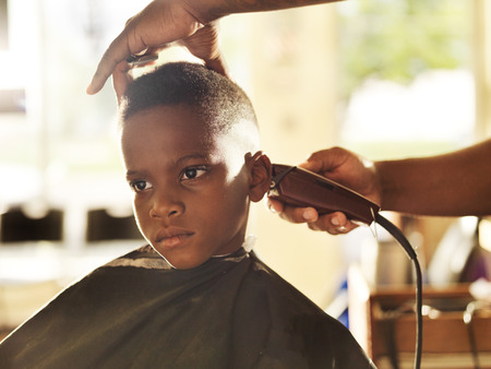 little boy getting his head shaved by barber