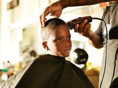 poco muchacho africano conseguir su corte de pelo en la barbería Foto de archivo