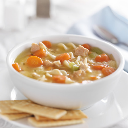 chicken noodle soup: bowl of chicken noodle soup on white table cloth