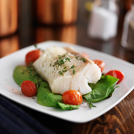 halibut: halibut with spinach, cherry tomatoes and thyme Stock Photo