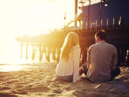 couple  amoureux: couple romantique assis ensemble sur la plage avec le coucher du soleil Banque d'images