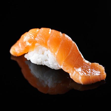 nigiri: single piece of salmon nigiri sushi on black background