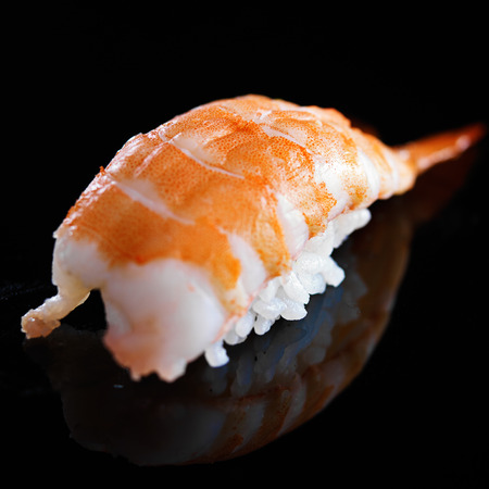 nigiri: a piece of shirmp nigiri sushi on black background