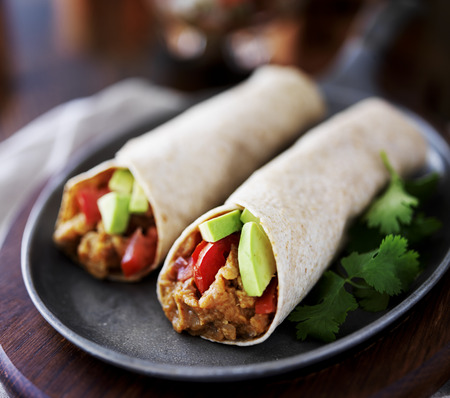 close up food: two vegan burritos with avocado, tomato and lentils