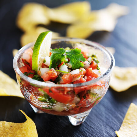 close up food: pico de gallo salsa with lime wedge and tortilla chips