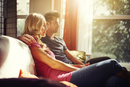 woman watching tv: couple at home on couch watching tv