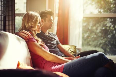 pareja viendo television: pareja en su casa en el sofá viendo la televisión Foto de archivo