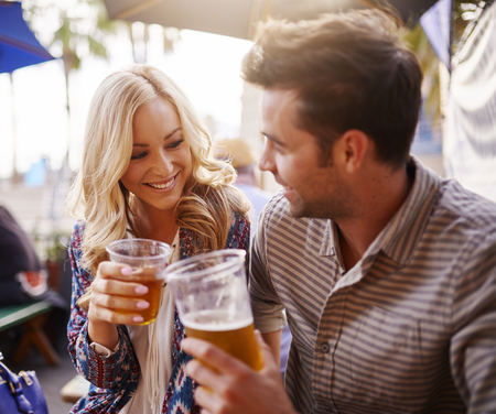 beer drinking: romantic couple drinking beer in plastic cups at outdoor bar Stock Photo