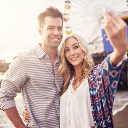 romatic couple taking selfie in front of santa monica with smartphone photo