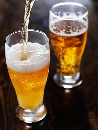背の高いマグカップ スレートのテーブルの上にビールを注ぐ