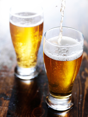 tall glass: two mugs of amber beer with foam head Stock Photo