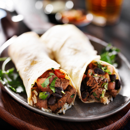 black dish: mexican beef steak burritos with black beans, rice, and salsa